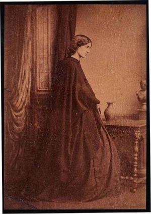 Jane Morris in cape, standing indoors
